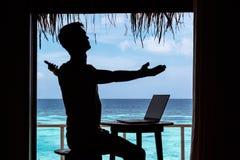 Силуэт молодого человека с оружиями поднял деятельность с компьютером на таблице Ясная голубая тропическая вода как предпосылка стоковые изображения