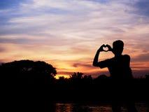Силуэт молодого человека формируя руку к форме сердца стоковая фотография