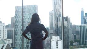 Силуэт молодой женщины идя и восхищает вид на город от окна в офисе 3840x2160 сток-видео