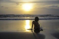 Силуэт молодой женщины лежа на песке смотря к горизонту захода солнца моря с красивым солнцем Стоковое фото RF