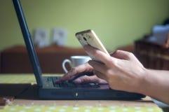 Силуэт молодой женщины работая от дома используя умные телефон и компьютер-книжку, руки ` s женщины используя умный телефон в инт Стоковые Изображения