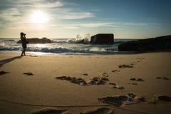 Силуэт молодой женщины стоя на сценарном песчаном пляже принимая фото красивого seascape Атлантического океана с волнами в солнеч стоковые фотографии rf