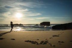 Силуэт молодой женщины стоя на сценарном песчаном пляже принимая фото красивого seascape Атлантического океана с волнами в солнеч стоковое фото rf