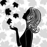 Силуэт молодой женщины с листьями летания Стоковые Изображения