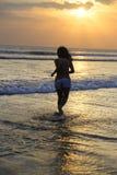 Силуэт молодой красивый и сексуальный азиатский бежать женщины свободный и счастливый имеющ потеху на пляже захода солнца в Бали Стоковое Изображение RF