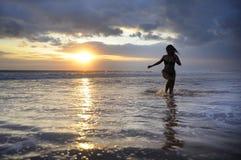 Силуэт молодой красивый и сексуальный азиатский бежать женщины свободный и счастливый имеющ потеху на пляже захода солнца в Бали Стоковая Фотография