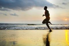 Силуэт молодой привлекательной пригонки атлетической и сильного черного афро американского человека бежать на тренировке пляжа за стоковое изображение rf