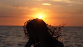Силуэт молодой счастливой женщины имеет музыку потехи слушая в наушниках на пляже на изумительном заходе солнца в замедленном дви видеоматериал