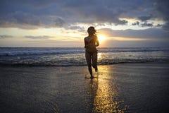 Силуэт молодой счастливой сексуальной азиатской женщины в бежать бикини возбужденный на пляже захода солнца Стоковое Изображение