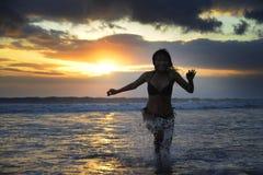 Силуэт молодой счастливой сексуальной азиатской женщины в бежать бикини возбужденный на пляже захода солнца Стоковая Фотография RF