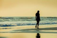 Силуэт молодой sporty женщины идя на seashore после идущей разминки на красивом пляже наслаждаясь светом захода солнца и ослабляе стоковое изображение rf