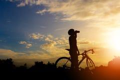 Силуэт мужчины велосипедиста ослабляет и питьевая вода с дорогой стоковое фото rf
