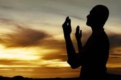 Силуэт мусульманского человека молит Стоковое Изображение RF