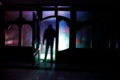 Силуэт неизвестной диаграммы тени на двери через закрытую стеклянную дверь Силуэт человека перед окном на ni Стоковые Изображения