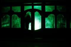 Силуэт неизвестной диаграммы тени на двери через закрытую стеклянную дверь Силуэт человека перед окном на ni Стоковое Изображение RF
