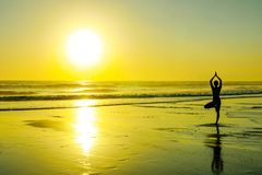 Силуэт неизвестной непознаваемой женщины стоя на йоге и раздумье морской воды пляжа практикуя смотря к солнцу на ho стоковые изображения