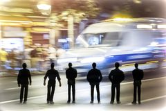 Силуэт несколько укомплектовывает личным составом смотреть машину скорой помощи на полной скорости ночью Стоковые Фотографии RF