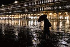 Силуэт ночи женщины с зонтиком на дождливой ночи в квадрате St Mark в Венеции с золотым светом стоковые фотографии rf