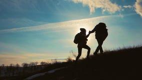 силуэт одина другого помощи пар пеший в горах Пары, один другого сыгранности помощи, помощь доверия, заход солнца акции видеоматериалы