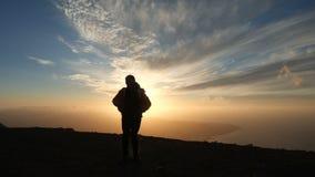 Силуэт оптимистического человека бежать и скача на красивый заход солнца в замедленном движении Сильный ветер заполняет куртку сток-видео