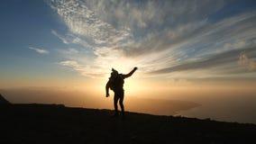 Силуэт оптимистического человека скача на красивый заход солнца в замедленном движении Сильный ветер заполняет куртку видеоматериал