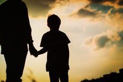 Силуэт отца и сына держа руки на заходе солнца Стоковое фото RF
