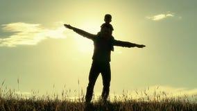 Силуэт отца и сына на предпосылке захода солнца Папа и сын показывают полет сами акции видеоматериалы