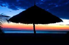 Силуэт парасоля на пляже над заходом солнца Стоковое Изображение RF