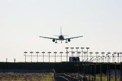 Силуэт пассажирского самолета на посадке с причаливая светами взлётно-посадочная дорожка Стоковое Изображение