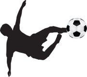 силуэт пинком футбола летания Стоковое фото RF