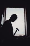 силуэт плотника работая с молотком против окна в плотничестве стоковые изображения