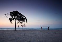 Силуэт покинутого зонтика пляжа на заходе солнца Заход солнца на море Стоковые Фотографии RF