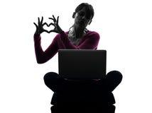 Силуэт портативного компьютера жеста сердца женщины вычисляя Стоковая Фотография