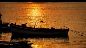 Силуэт пристани, шлюпки с установкой солнца в предпосылке с пасмурным и красочным небом, солнечностью Starlight на поверхности во Стоковые Изображения RF