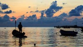 Силуэт пристани, шлюпки с установкой солнца в предпосылке с пасмурным и красочным небом, солнечностью Starlight на поверхности во Стоковое Изображение RF