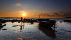 Силуэт пристани, шлюпки с установкой солнца в предпосылке с пасмурным и красочным небом, солнечностью Starlight на поверхности во Стоковые Фотографии RF