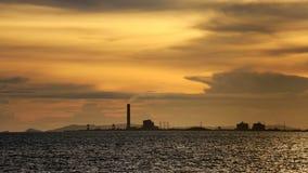 Силуэт промышленного с установкой солнца в предпосылке с пасмурным и красочным небом, солнечностью Starlight на поверхности воды Стоковые Изображения RF