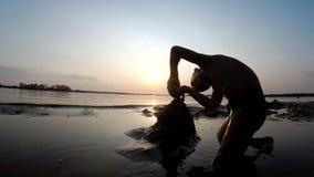 Силуэт ребенка на пляже строя замок песка на заходе солнца сток-видео