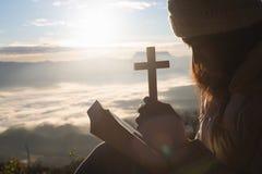 Силуэт руки женщины держа святой подъем христианского креста со светлой предпосылкой захода солнца стоковая фотография