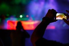 Силуэт руки используя телефон камеры для того чтобы сфотографировать и видео на концерте в реальном маштабе времени party Стоковые Изображения RF
