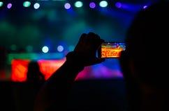 Силуэт руки используя телефон камеры для того чтобы сфотографировать и видео на концерте в реальном маштабе времени party Стоковая Фотография RF