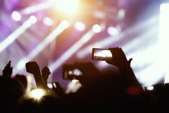 Силуэт рук используя телефон камеры для того чтобы принять изображения и видео на концерт в реальном маштабе времени Стоковое фото RF