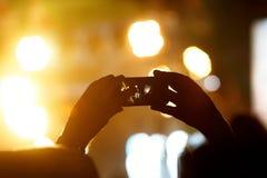 Силуэт рук используя телефон камеры для того чтобы принять изображения и видео на концерт в реальном маштабе времени Стоковое Фото