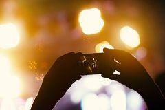 Силуэт рук используя телефон камеры для того чтобы принять изображения и видео на концерт в реальном маштабе времени Стоковое Изображение RF