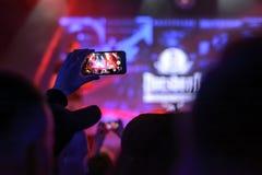Силуэт рук с smartphone на концерте Стоковые Изображения RF