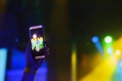 Силуэт рук с smartphone на концерте Стоковые Фотографии RF