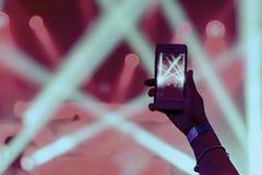 Силуэт рук с smartphone на концерте Стоковое Изображение RF