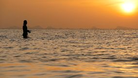 Силуэт рыболова в действии закручивая на время захода солнца Традиционные азиатские занятие и путь получать еду сток-видео