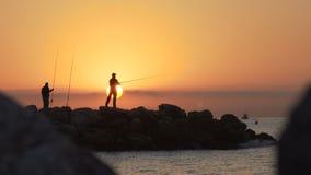Силуэт рыболова, рыбная ловля человека на море от утеса на заходе солнца видеоматериал