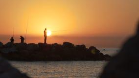 Силуэт рыболова, рыбная ловля человека на море от утеса на заходе солнца 120fps акции видеоматериалы